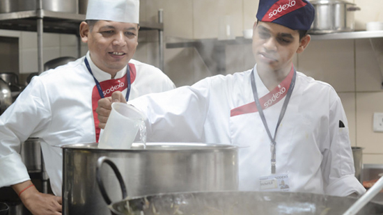 Two sodexo chefs pouring liquid in to a saucepan